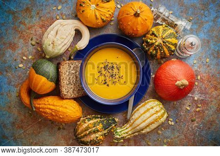 Compositon with autumn classic food. Tasty homemade pumpkin soup decorated with black seed. Flat lay over rusty background. Various kinds of mini pumpkins.