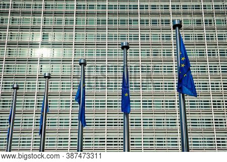 Helplessly drooping EU European Union flags with the European Comission building in Background. Brussles, Belgium