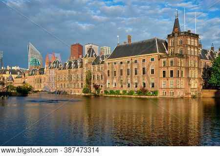 View of the Binnenhof House of Parliament and the Hofvijver lake with downtown skyscrapers in background. The Hague, Netherlands