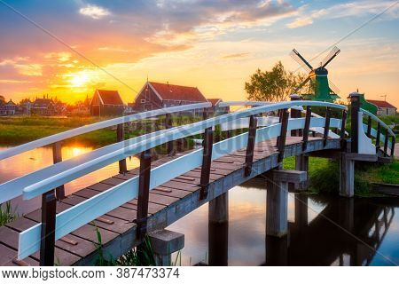 Netherlands rural scene - bridge over canal and windmills at famous tourist site Zaanse Schans in Holland on sunset with dramatic sky. Zaandam, Netherlands