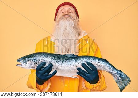 Old senior man with grey hair and long beard wearing raincoat holding fresh salmon looking at the camera blowing a kiss being lovely and sexy. love expression.