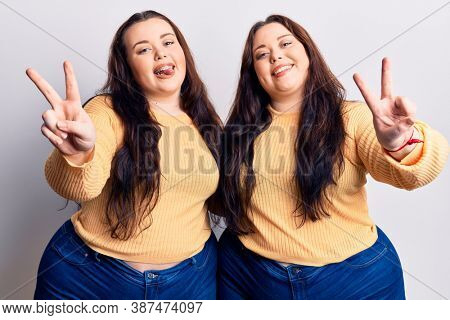 Young plus size twins wearing casual clothes smiling with tongue out showing fingers of both hands doing victory sign. number two.