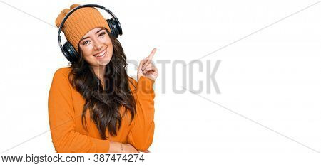 Beautiful brunette young woman listening to music using headphones with a big smile on face, pointing with hand and finger to the side looking at the camera.