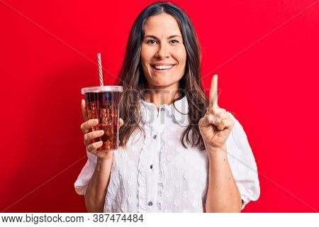 Beautiful brunette woman drinking cola refreshment beverage using straw over red background smiling with an idea or question pointing finger with happy face, number one
