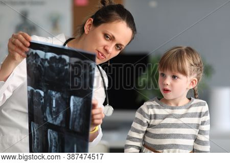 Woman Doctor Shows Child Patient An Xray In Clinic. Use Of Radiation Diagnostics Of Diseases Of Skel