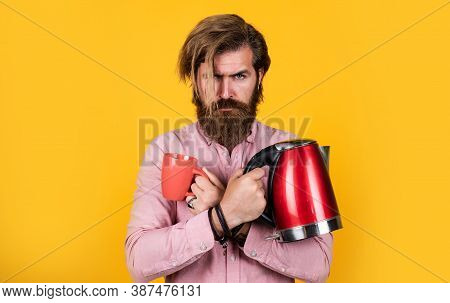 Brutal Guy With Electric Kettle. Warm Your Day. Bearded Man. Drink Hot Beverage. Presenting Kitchen