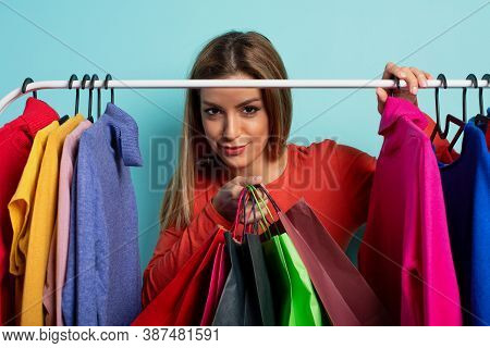 Blonde Woman Chooses The Clothes To Buy In A Store. Concept Of Shopping And Shopaholic.
