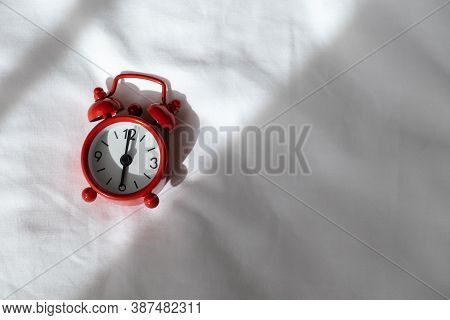 Red Analog Clock On White Rumpled Sheets. Top View, Flat Lay, Copy Space. Horizontal. Concept Of Awa