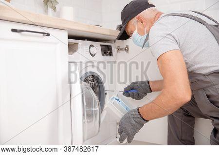 Working Man In Medical Mask Plumber Repairs Washing Machine In Kitchen