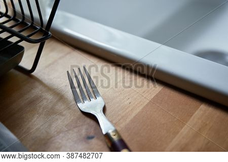 Fork lying by the basin on a kitchen counter. Maybe used, maybe not