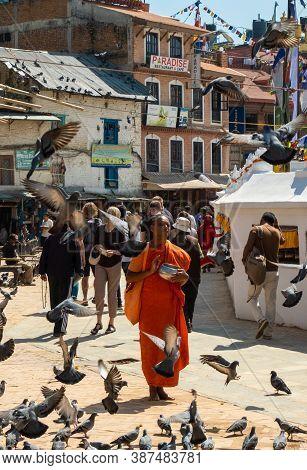 Kathmandu, Nepal - October 2019: A Saffron-robed Buddhist Monk With A Begging Bowl Recites Mantras O