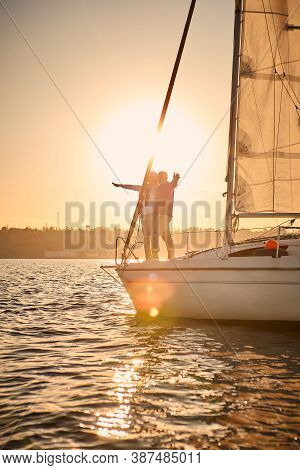 Romantic Senior Couple Enjoying Sailing Together At Sunset, Stretching Hands Out Against The Sky Whi