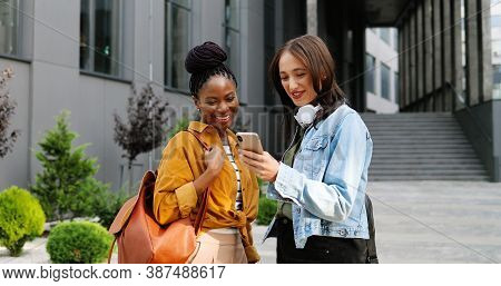 Mixed-races Females Talking And Watching Something On Mobile Phone At Street In City. Beautiful Mult