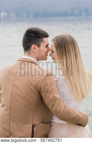 Salo, Italy - 02.02.2020. Romantic Young Couple Sitting On The River Dock And Walking On The Lake Ba