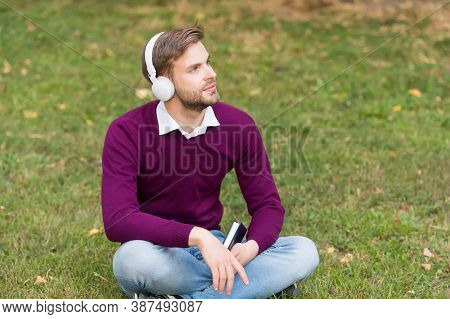Handsome Guy In Earphones Relax In Park. Modern Life Technology. Student Get Information From Book.