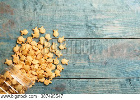 Overturned Jar With Goldfish Crackers On Blue Wooden Table, Flat Lay. Space For Text