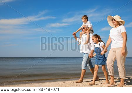 Cute Little Children With Grandparents Spending Time Together On Sea Beach