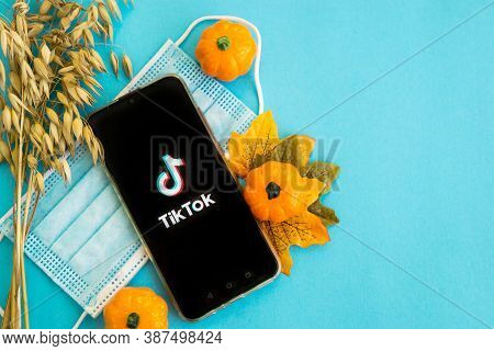 Tver, Russia - September 25, 2020, Medical Mask, Pumpkins And Tik Tok Logo On The Smartphone Screen