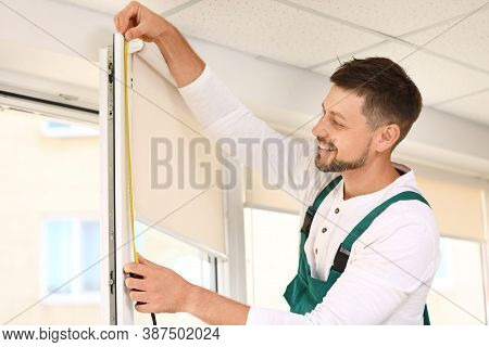 Handyman With Tape Measure Installing Roller Window Blind Indoors