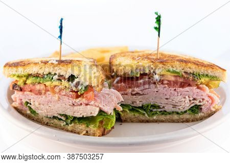 Generous Serving Meal Of A Hearty Layered Meat, Avocado, Bacon, Sandwich Stacked Tall On The Plate.