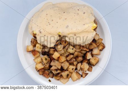 Overhead View Of Generous Serving Meal Of A Hearty Biscuit, Eggs, Potatoes Covered In Country Gravy.