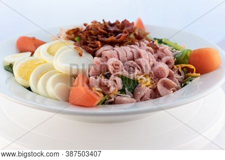 Generous Serving Meal Of A Hearty Breakfast Salad Loaded With Topping In A Large Bowl.