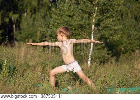 Young Boy Child Practices Yoga, Standing Of Yoga Warrior Pose, Exercising Virabhadrasana Pose Outdoo