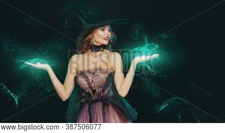 Portrait of a beautiful charming witch in a hat and elegant dress conjuring surrounded by magic lights. Halloween celebration, party.
