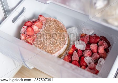 Frozen Strawberry Cake And Strawberries In The Freezer Drawer Of The Fridge. Concept Of The Convenie