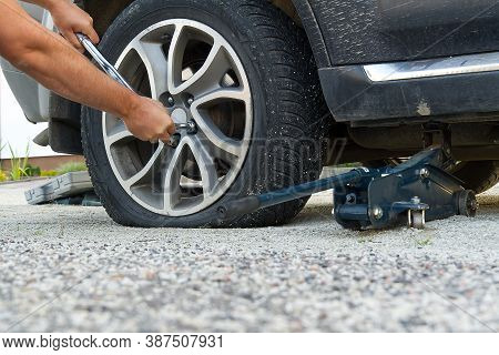 Man Changing Wheel. Tire Changer Changing Flat Car Tire. Help On Road Concept. Mechanic Hands Unscre