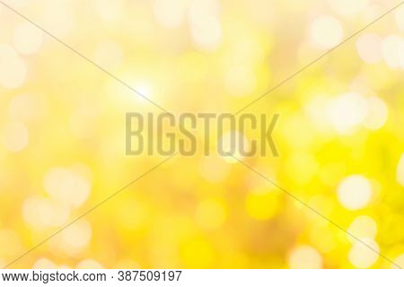 Natural Yellow Background Blurring Warm Colors And Bright Gold Sunlight. Bokeh Or Christmas Backgrou