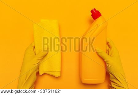 Hands In Yellow Gloves Hold A Yellow Rag And A Yellow Bottle Of Toilet Liquid On A Yellow Background