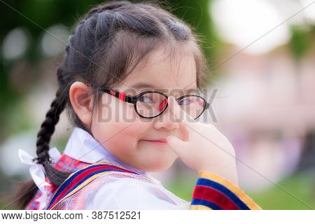 Schoolgirl Wearing Young Girl's Uniform. Child Uses The Index Finger To Push The Glasses She Is Wear