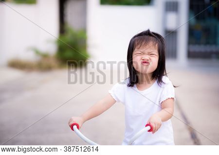 Preschool Asian Little Child Girl Make A Playful Face. Children Wrapped Up The Mouth And  Ride A Bic