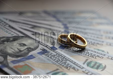 Wedding Rings On The Background Of 100 Dollars Bills. Marriage Conctract Or Prenuptial Agreement Con