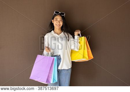 Young Asian women happily carry colorful shopping bags to shop in the mall or shopping center, Sale