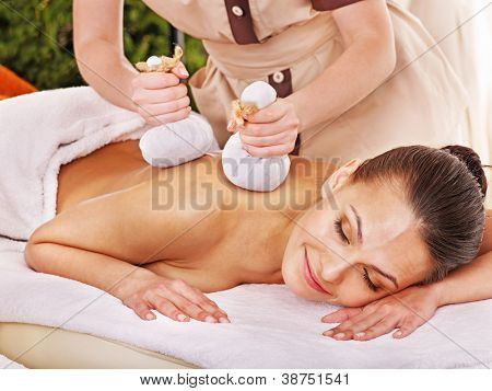 Woman getting herbal ball massage treatments  in spa.