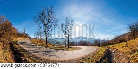 Serpentine Turnaround On Foggy Sunrise. Naked Trees On Grassy Hillsides Under Gorgeous Cloudy Sky Ov