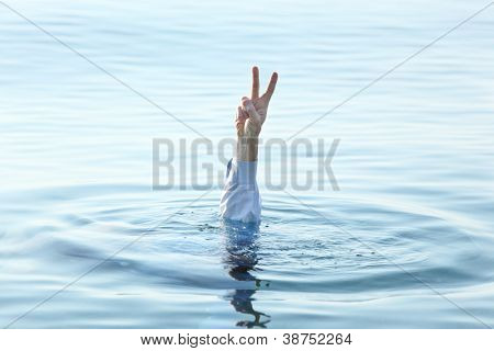 Sinking man showing Victory sign