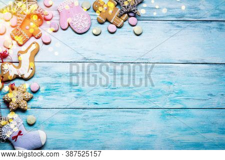 Blue wooden background with christmas traditional ginger cookies. Christmas or New Year holiday background. Top view.