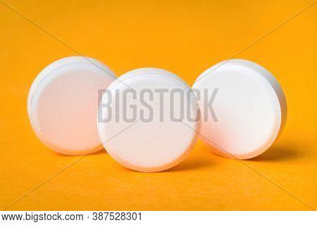 Close-up Of White Pills Isolated On Orange Background