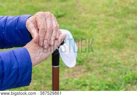 Old Lady Holding Walking Stick On Grass Background. Close Up Of Elderly Hands Resting On Stick In Pa
