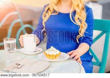 Charming Serene Pregnant Woman In Blue Dress Eating Appetizing Cake With Cream In Outdoor Cafe Or Te