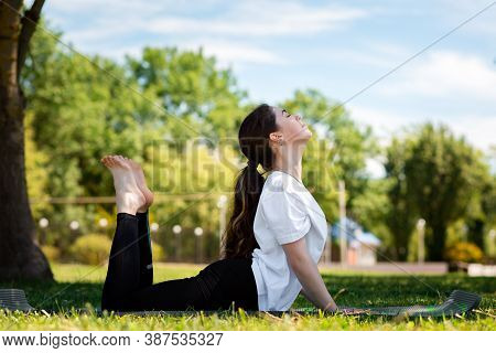 Yoga. A Young Pretty Woman In Sports Clothing, Performs An Exercise Lying On The Mat. Park In The Ba