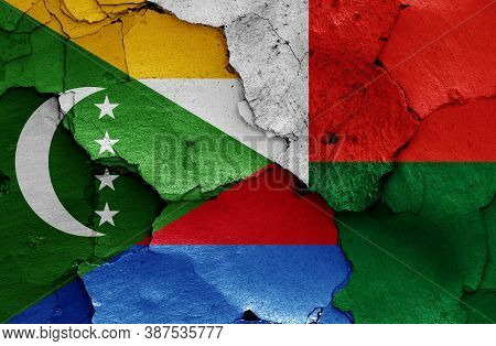 Flags Of Comoros And Madagascar Painted On Cracked Wall