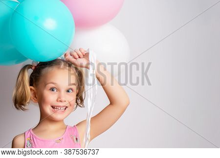 Little Cute Smiling 5 Year Old Girl Holding A Bunch Of Colorful Balloons.