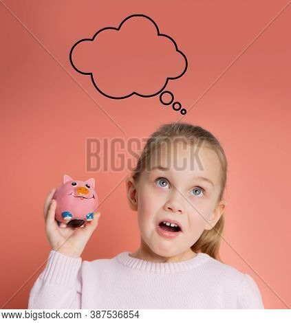 Surprised Girl With A Piggy Bank Thinking Of Desires Thought Cloud On A Pink Background