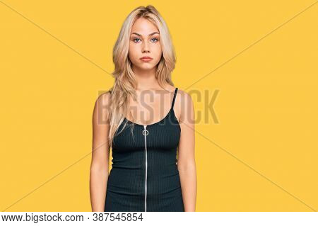 Young blonde wearing elegant and sexy look with serious expression on face. simple and natural looking at the camera.