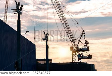 Silhouette Construction Crane Against Sunset Sky. Crane Use Reel Lift Up Equipment In Construction S