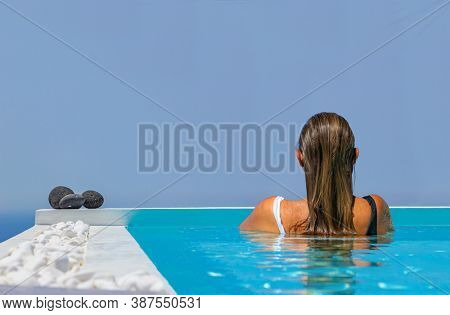 Woman at the swimming pool on the island of Santorini in Greece on a luxury holidays with view on the caldera